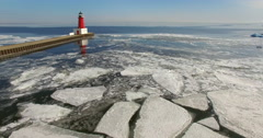 Icy Harbor Flyby of Menominee North Pier Lighthouse Stock Footage