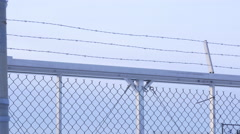 layers of chain link and barbed wire fence in winter day - stock footage