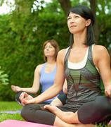 Two mature women keeping fit by doing yoga in the summer - stock photo