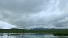 Fisherman Fly Fishing in Swedish Lake, Shallow, Mountains in Background. Wide - stock footage