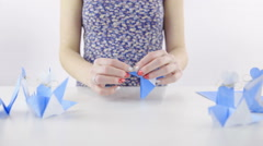 Finished folding origami bird from turquoise paper 4K Stock Footage