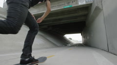 Skater Pushing Down Bike Trail Under Bridge 4K Stock Footage