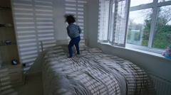 4K Happy little boy having fun at home, jumping up and down on the bed - stock footage