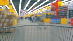Supermarket interior with customers and trolley, blurred background Stock Footage