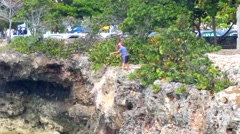 SANTO DOMINGO, DOMENICAN REPUBLIC FEBRUARY 04 a man fishing at a huge cliff i Stock Footage