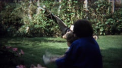 1973: Mom rocks toddler play backyard game backwards. - stock footage