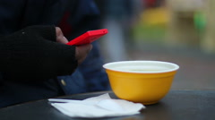 Poor man having cheap meal at street snack bar, texting message on smartphone Stock Footage