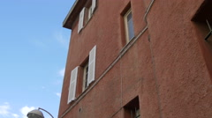Old red building with white shutters in Nice - stock footage