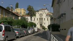 Driving a car and riding a bike near a church in Nice Stock Footage