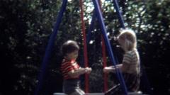1971: Blonde caucasian kids playground backyard see saw swing. Stock Footage