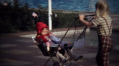 1971: Kid sister pushing baby stroller raggedy anne andy dolls. Stock Footage