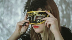 Woman putting black, carnival mask on her face and tie it Stock Footage