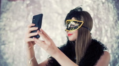 Beautiful girl wearing carnival mask and doing selfies on smartphone Stock Footage