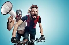 Two hilarious cyclists involved in a contest - stock photo