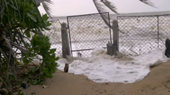 Slow motion of rising sea levels crashing through a closed gate Stock Footage