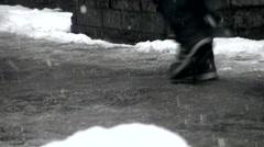 Legs of people walking on snowy, slushy city street in winter in 4K Video. - stock footage