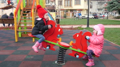 Children ride on balance swing happily enjoying the playground Stock Footage