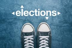 Young man standing on the street, elections sign on road Stock Photos
