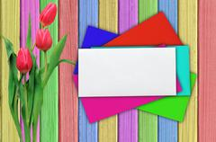 Pink tulips and colorful envelops over shabby paint wooden table - stock photo