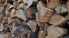 Walking along firewood prepared for winter stockpiled by a house wall Stock Footage