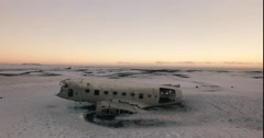 Aerial shot, fly over wrecked DC-3 plane in wide open snow covered landscape Stock Footage
