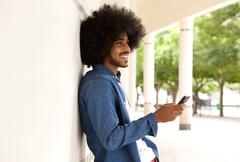 Smiling modern man standing outside with cell phone - stock photo