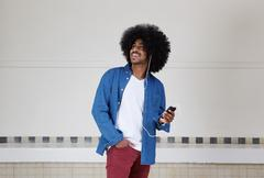 Cool black guy listening to music on mobile phone - stock photo