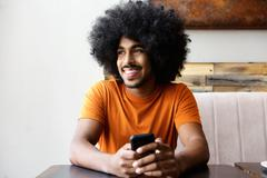 Smiling african american man sitting at table with mobile phone - stock photo