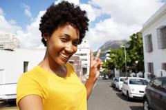 Smiling young woman gesturing peace sign Stock Photos