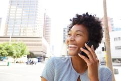 Cheerful young woman in the city making a phone cal - stock photo
