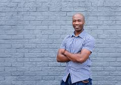 Smiling african american man standing with arms crossed Stock Photos