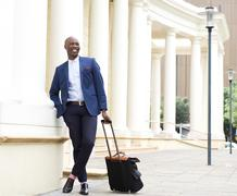 Handsome businessman standing outdoors with bag - stock photo