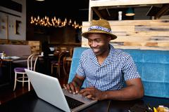 African american man sitting at a cafe and working on a laptop Stock Photos