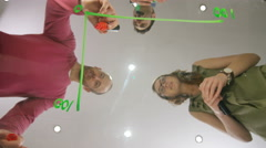 4K Low angle view looking up, casual business team drawing chart on glass table Stock Footage