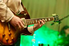 Musician plays on guitar in grey jacket - stock photo