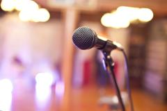Close-up of a microphone in a concert hall on the background of blurred light - stock photo