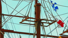 Masts and rigging of three-masted sailing ship over the bright blue sky - stock footage