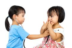 Asian Little Chinese Girls Playing as Doctor and Patient with Stethoscope Stock Photos