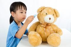 Asian Little Chinese Girl Playing Doctor with Teddy Bear Stock Photos