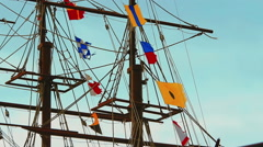 Three-masted frigate ship with colorful flags fluttering in the wind - stock footage