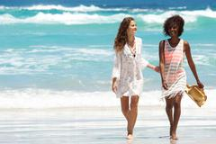 Female friends walking barefoot by the water on a beach - stock photo