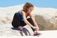 Active young woman tying shoelace at the beach Stock Photos