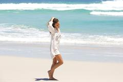 Young woman in contemplation walking on the beach - stock photo