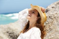 Young woman laughing with cowboy hat at the beach - stock photo
