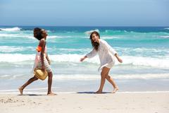 Female friends walking and smiling at the beach - stock photo