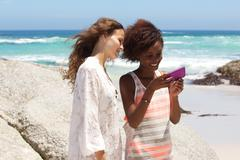 Two female friends at the beach looking at mobile phone - stock photo