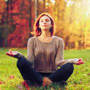 Young female meditate in park Stock Photos