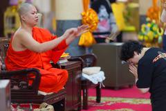 Buddhist monk blessing woman - stock photo