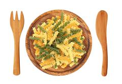 Pasta on wooden plate, fork and knife isolated on white background - stock photo