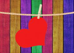 Red heart hang on clothespin over painted wooden background Stock Photos